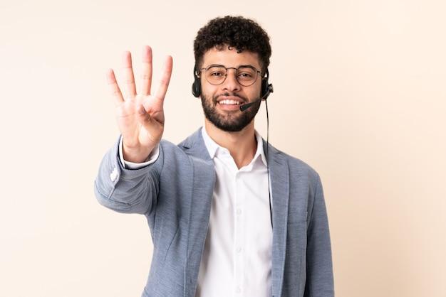 Telemarketer marokański mężczyzna pracujący z zestawem słuchawkowym na białym tle na beżowym tle szczęśliwy i liczący cztery palcami