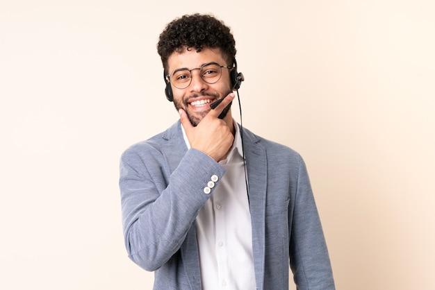 Telemarketer marokański mężczyzna pracujący z zestawem słuchawkowym na białym tle na beżowym tle szczęśliwy i uśmiechnięty