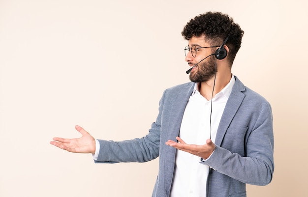 Telemarketer marokański mężczyzna pracujący z zestawem słuchawkowym na białym tle na beżowym tle z wyrazem zaskoczenia, patrząc z boku