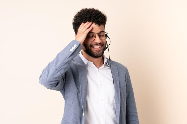 Telemarketer marokański mężczyzna pracujący z zestawem słuchawkowym odizolowanym na beżowo dużo się uśmiecha