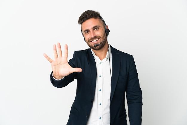 Telemarketer mężczyzna pracujący z zestawem słuchawkowym na białym tle licząc pięć palcami