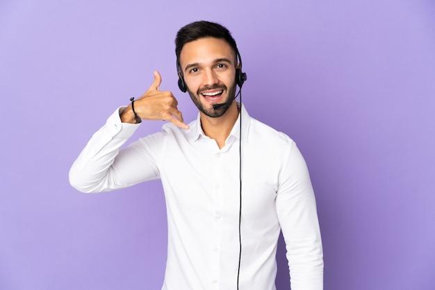 Telemarketer mężczyzna pracujący z zestawem słuchawkowym na białym tle na fioletowej ścianie dokonywanie gestu telefonu. oddzwoń do mnie znak