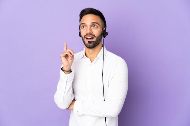 Telemarketer mężczyzna pracujący z zestawem słuchawkowym na białym tle na fioletowym tle myśli pomysł wskazując palcem w górę