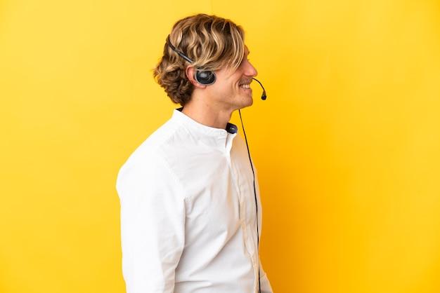 Telemarketer mężczyzna pracujący z zestawem słuchawkowym na białym tle na żółtej ścianie patrząc z boku