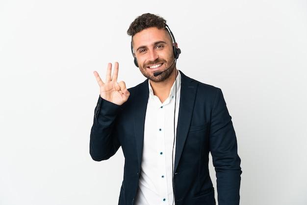 Telemarketer mężczyzna pracujący z zestawem słuchawkowym na białym tle przedstawiający znak ok palcami