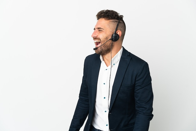 Telemarketer mężczyzna pracujący z zestawem słuchawkowym na białym tle śmiejący się w pozycji bocznej