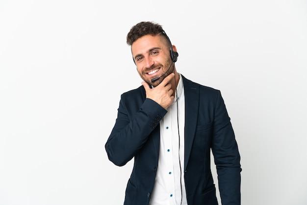 Telemarketer mężczyzna pracujący z zestawem słuchawkowym na białym tle szczęśliwy i uśmiechnięty
