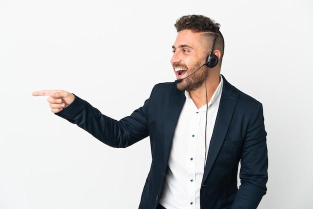 Telemarketer mężczyzna pracujący z zestawem słuchawkowym na białym tle wskazujący palec na bok i prezentujący produkt