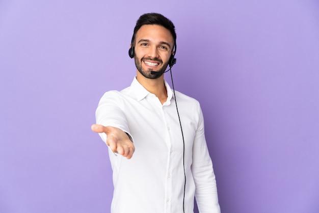 Telemarketer mężczyzna pracujący z zestawem słuchawkowym na fioletowym tle, ściskając ręce za zamknięcie dobrej oferty