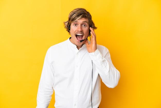 Telemarketer mężczyzna pracujący z zestawem słuchawkowym na żółtej ścianie z zaskoczeniem i zszokowanym wyrazem twarzy