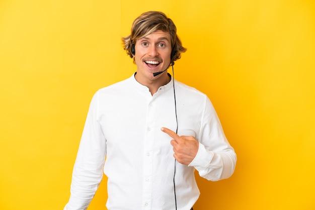 Telemarketer mężczyzna pracujący z zestawem słuchawkowym na żółtym tle z wyrazem twarzy zaskoczenia