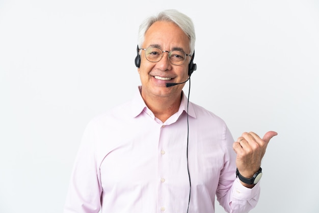 Telemarketer mężczyzna w średnim wieku pracujący z zestawem słuchawkowym na białym tle wskazującym na bok, aby zaprezentować produkt