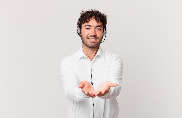 Telemarketer uśmiechający się radośnie z przyjaznym, pewnym siebie, pozytywnym spojrzeniem, oferujący i pokazujący przedmiot lub koncepcję
