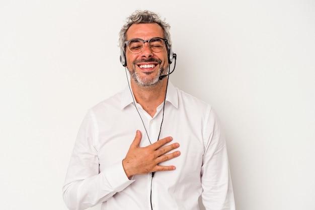 Telemarketer w średnim wieku kaukaski mężczyzna na białym tle śmieje się głośno trzymając rękę na klatce piersiowej.