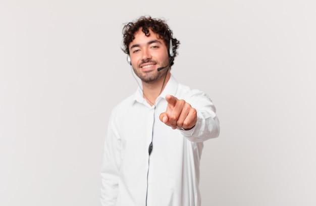 Telemarketer wskazujący na aparat z zadowolonym, pewnym siebie, przyjaznym uśmiechem, wybierający ciebie