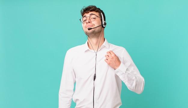 Telemarketer wyglądający arogancko, odnoszący sukcesy, pozytywny i dumny, wskazujący na siebie