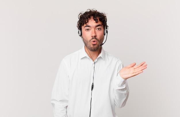 Telemarketer wyglądający na zaskoczonego i zszokowanego, z opuszczoną szczęką, trzymający przedmiot z otwartą dłonią z boku