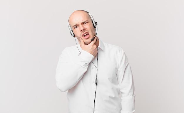 Telemarketer z szeroko otwartymi ustami i oczami i ręką na brodzie, nieprzyjemnie zszokowany, mówiący co lub wow