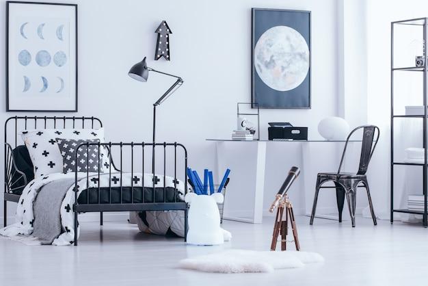 Teleskop i czarne krzesło przy biurku we wnętrzu sypialni nastolatka z metalowym łóżkiem i plakatem księżyca na białej ścianie