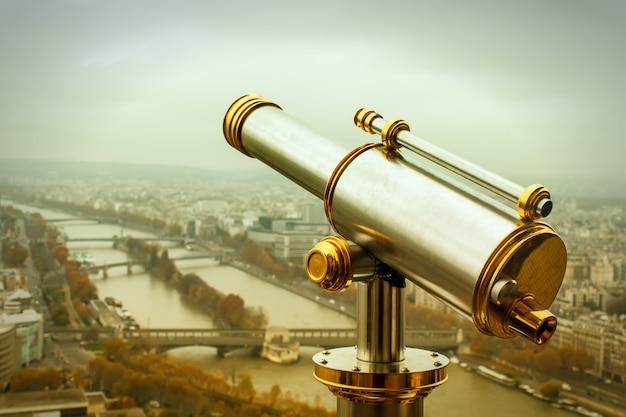 Teleskop na monety na wieży eiffla w paryżu. stonowany obraz