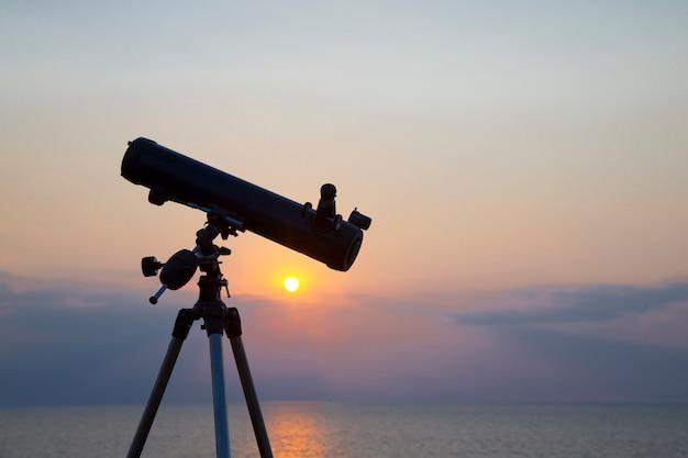 Teleskop sylwetka na pomarańczowy zachód słońca