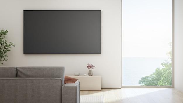 Telewizor na białej ścianie przeciwko sofie w domu lub willi.