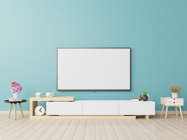 Telewizor na szafce w nowoczesnym salonie ma rośliny i książkę na niebieskim tle ściany.