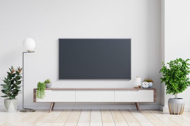 Telewizor na szafce w nowoczesnym salonie na tle białej ściany.