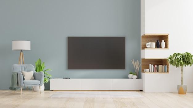 Telewizor na szafce w nowoczesnym salonie, wnętrze jasnego salonu z fotelem na pustej niebieskiej ścianie