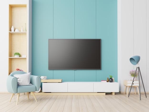 Telewizor na szafce w nowoczesnym salonie z fotelem na niebieskim tle ściany.