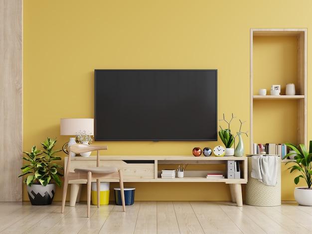 Telewizor na szafce w nowoczesnym salonie z lampą, stołem, kwiatkiem i rośliną na żółtej ścianie