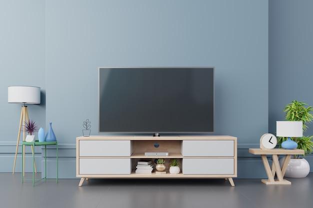 Telewizor na szafce wnętrze nowoczesny pokój z roślinami, półka, lampa na ciemnoniebieskiej ścianie.