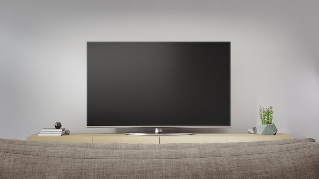 Telewizor przy białej ścianie jasnego salonu i sofy