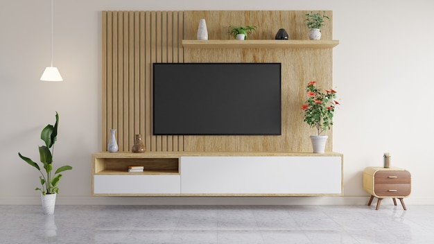 Telewizor zamontowany jest na drewnianej ścianie, na półce stoi wazon i książki, w salonie doniczka i stolik boczny.