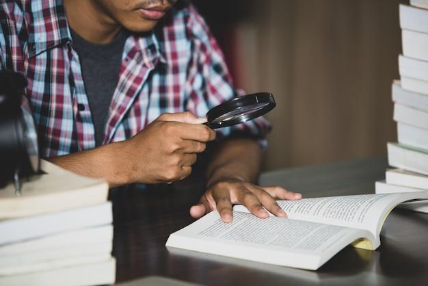 Temat edukacyjny: zbliżenie student ogląda przez szkło powiększające książkę