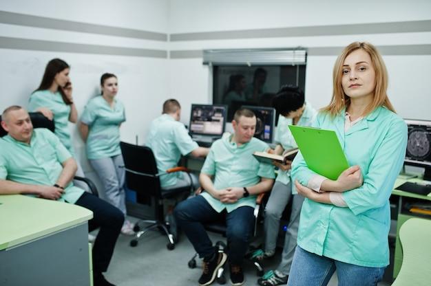 Temat medyczny. portret lekarki ze schowkiem przed grupą lekarzy spotykających się w gabinecie mri w centrum diagnostycznym w szpitalu.