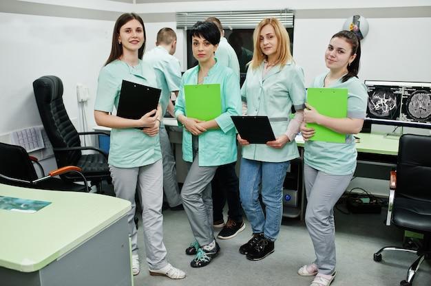 Temat medyczny.sala obserwacyjna z tomografem komputerowym. grupa lekarek ze schowkami spotykająca się w gabinecie rezonansu magnetycznego w centrum diagnostycznym w szpitalu.