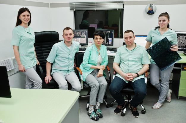 Temat medyczny.sala obserwacyjna z tomografem komputerowym. grupa lekarzy spotykająca się w gabinecie rezonansu magnetycznego w centrum diagnostycznym w szpitalu. przytrzymaj zdjęcie rentgenowskie.