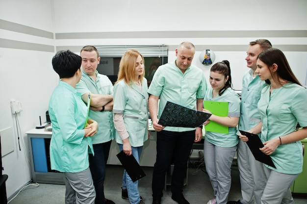 Temat medyczny.sala obserwacyjna z tomografem komputerowym. grupa lekarzy spotykających się w gabinecie rezonansu magnetycznego i patrzących na prześwietlenie w centrum diagnostycznym w szpitalu.