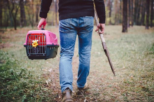 Temat nielegalnego grzebania zwierząt w lesie. samoobsługowy pochówek zwierzaka w lesie. mężczyzna niesie transporter z martwym kotem lub psem i dużą łopatą do zakopania w ziemi w lesie. rip zwierzę domowe.