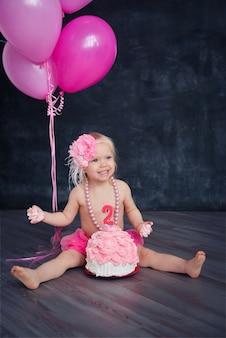 Tematyczne urodziny dla wesołej, emocjonalnej dziewczyny blondynki rozbijają ciasto na różowo