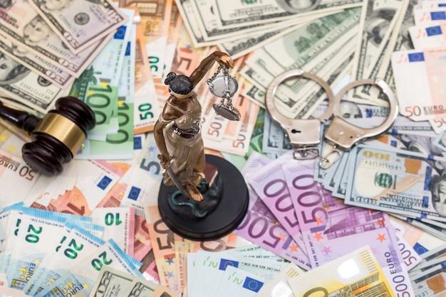 Temida i kajdanki, młotek na bacnkground banknotów euro i dolarowych