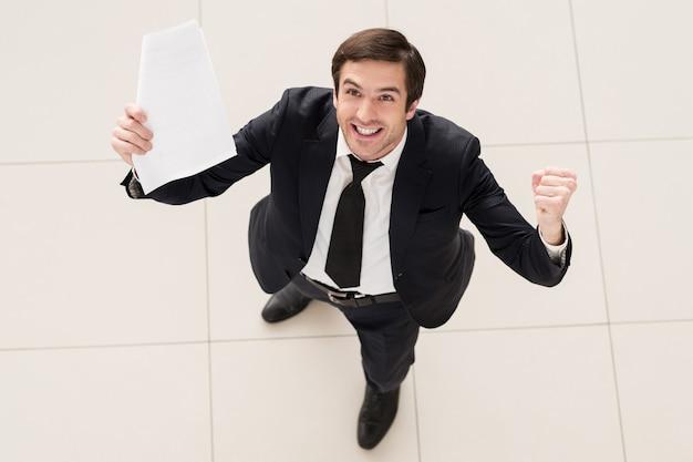 Ten kontrakt jest mój! widok z góry podekscytowanego młodego mężczyzny w formalnej odzieży, trzymającego papier w jednej ręce i gestykulującego
