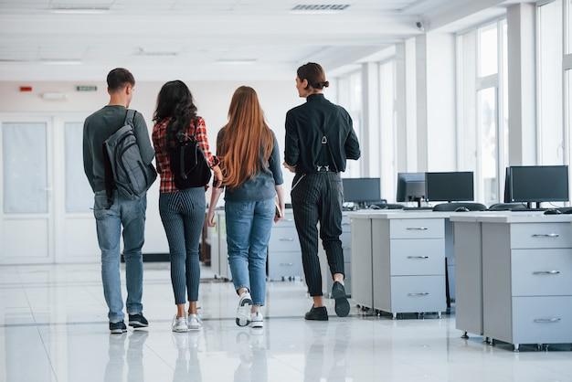 Ten pokój wkrótce będzie pusty. grupa młodych ludzi chodzących po biurze w czasie przerwy
