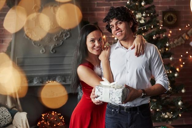 Ten prezent jest dla ciebie. piękna para świętuje nowy rok w urządzonym pokoju z choinką i kominkiem za.