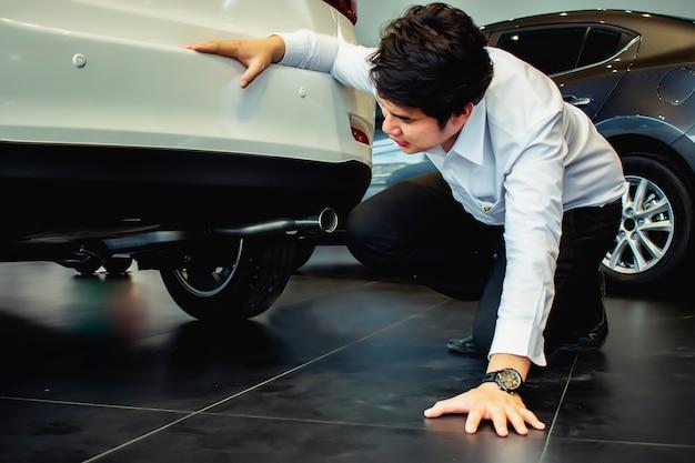 Ten samochód inspekcyjny saleman kontroli zawieszenia lub pod samochodem