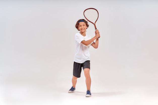Tenis to zabawne, pełnometrażowe ujęcie szczęśliwego nastoletniego chłopca trzymającego rakietę tenisową i uśmiechniętego na białym tle