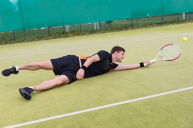 Tenisista mężczyzna ubrany w odzież sportową w akcji podczas gry spadł na korcie