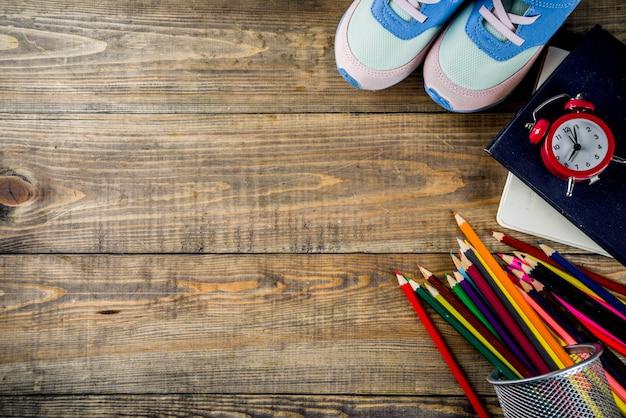 Tenisówki dla dzieci, książki, kolorowe kredki i budzik na tle drewniane biurko