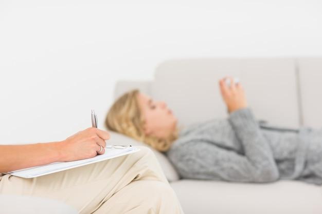 Terapeuta bierze notatki na jej pacjencie na kanapie
